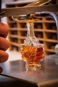 filling a maple leaf bottle with syrup