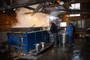 people monitoring the evaporator inside the Purinton sugarhouse