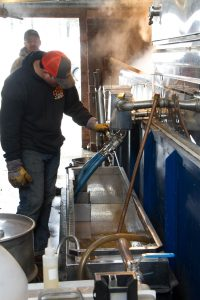 Cody draining the maple syrup from the eveporator